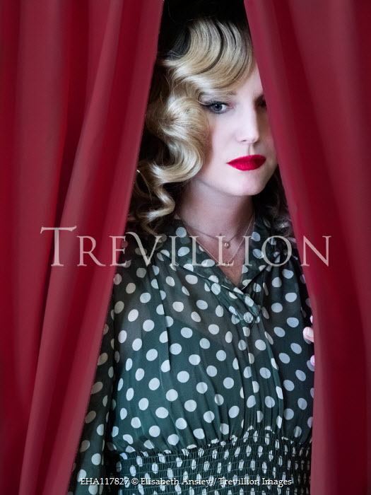 Elisabeth Ansley BLONDE WOMAN IN SPOTTY DRESS BEHIND RED CURTAINS Women
