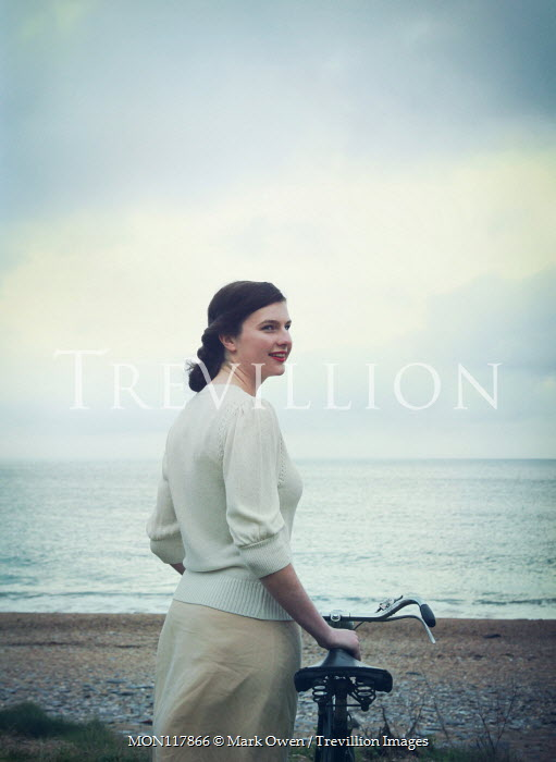Mark Owen SMILING WOMAN WITH BICYCLE BY OCEAN Women