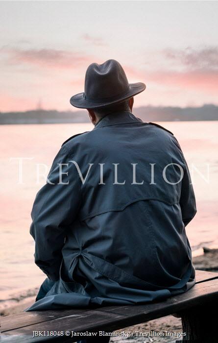 Jaroslaw Blaminsky RETRO MAN IN HAT SITTING BY LAKE AT SUNSET Men