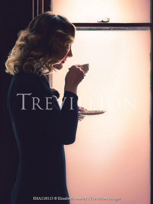 Elisabeth Ansley WOMAN STANDING BY WINDOW DRINKING TEA Women