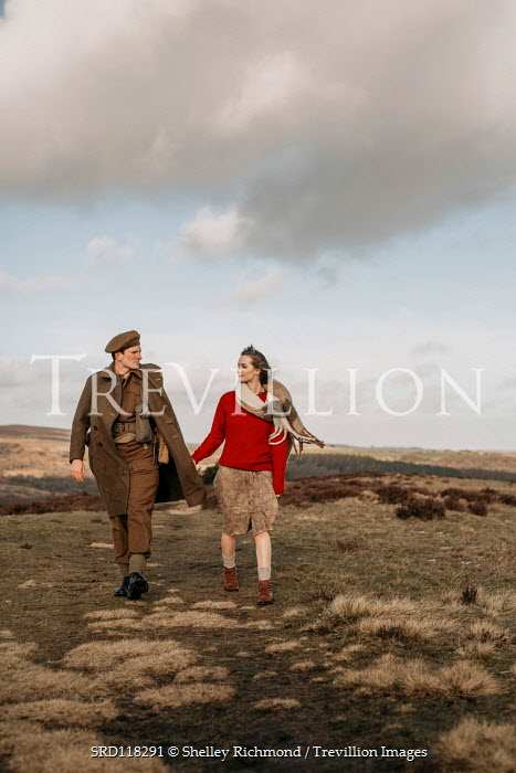Shelley Richmond Young woman and soldier holding hands while walking in field