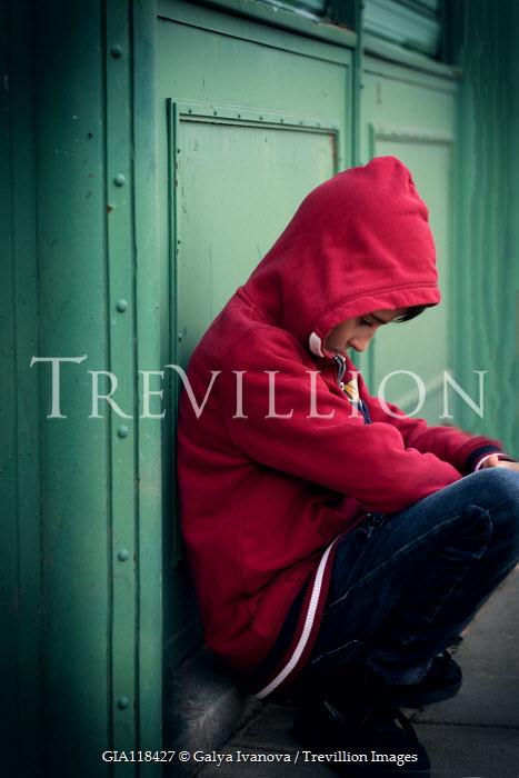 Galya Ivanova SAD BOY IN RED HOODIE CROUCHING BY DOORS Children