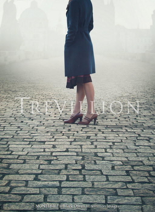 Mark Owen WOMAN STANDING ON FOGGY COBBLED STREET Women