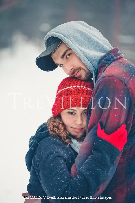 Evelina Kremsdorf YOUNG COUPLE EMBRACING OUTDOORS IN SNOW Couples