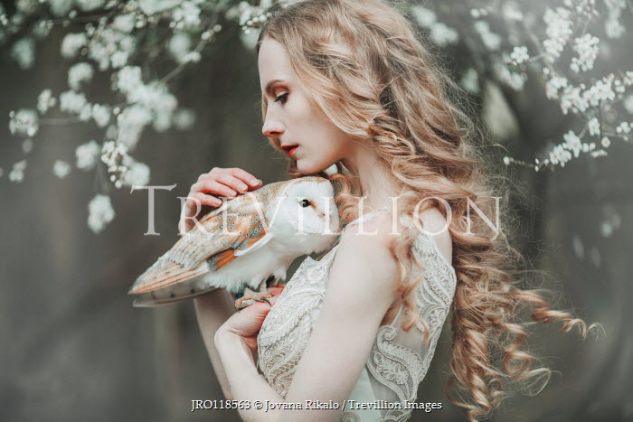 Jovana Rikalo WOMAN HOLDING OWL BY TREE IN BLOSSOM Women