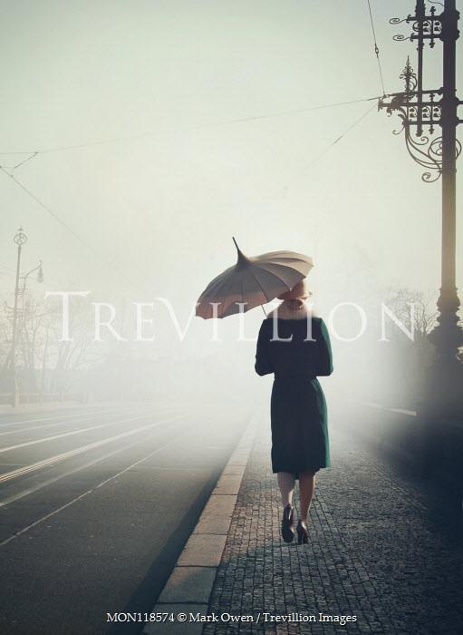 Mark Owen WOMAN WITH UMBRELLA WALKING BY FOGGY ROAD Women