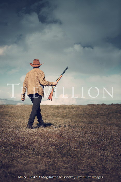 Magdalena Russocka cowboy man with rifle walking in field with mountains