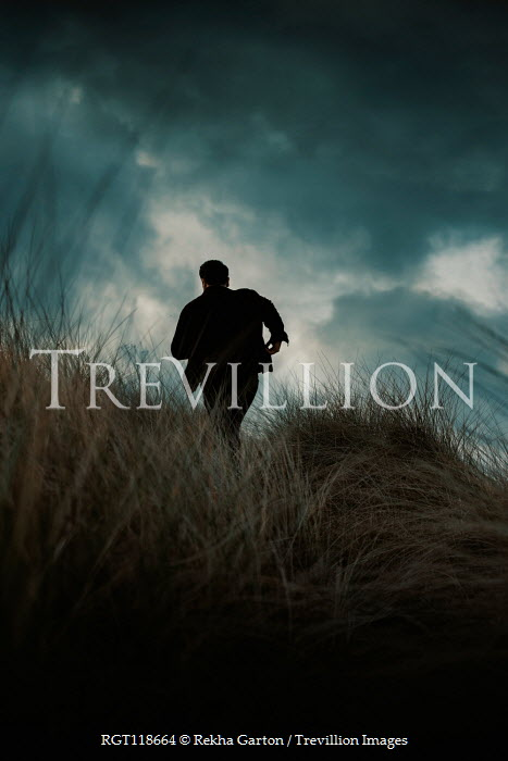 Rekha Garton MAN RUNNING IN LONG GRASS WITH STORMY SKY Men