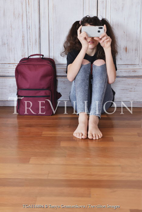 Tanya Gramatikova Teenage girl with smart phone sitting by backpack