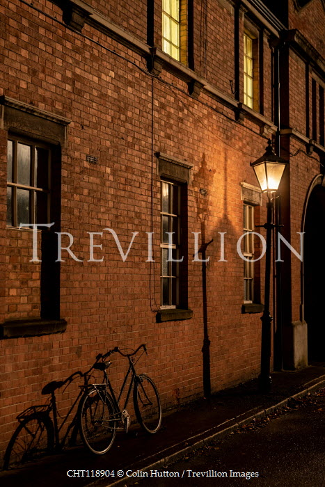 Colin Hutton BICYCLE AGAINST OLD BRICK BUILDING AT NIGHT Miscellaneous Transport