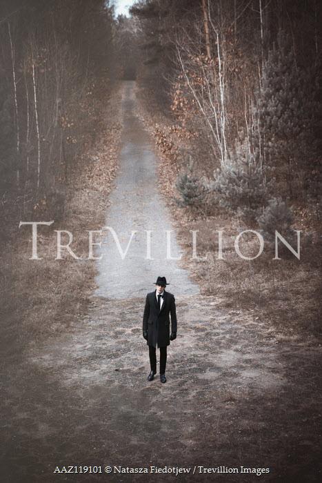 Natasza Fiedotjew Man in black coat and hat standing on walkway in woods