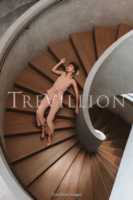 Muna Nazak WOMAN LYING ON MODERN STAIRCASE FROM ABOVE Women