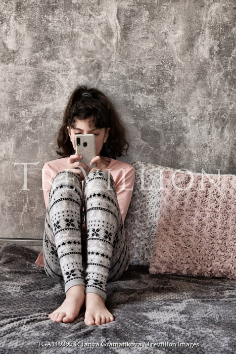 Tanya Gramatikova Teenage girl text messaging on bed