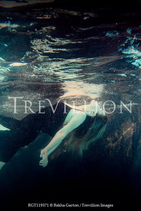 Rekha Garton Young woman in black dress underwater