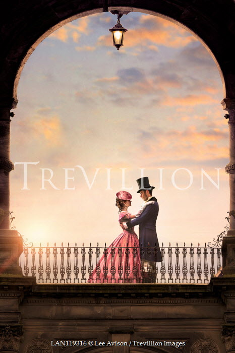 Lee Avison victorian couple embracing beneath an archway at sunset