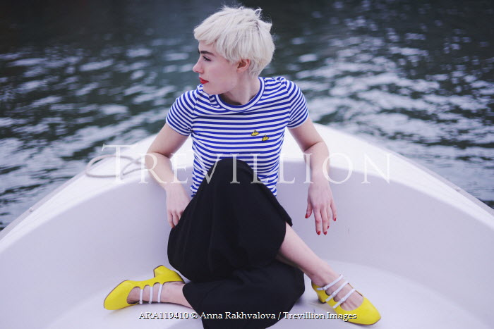 Anna Rakhvalova Young woman in striped shirt sitting in boat Women
