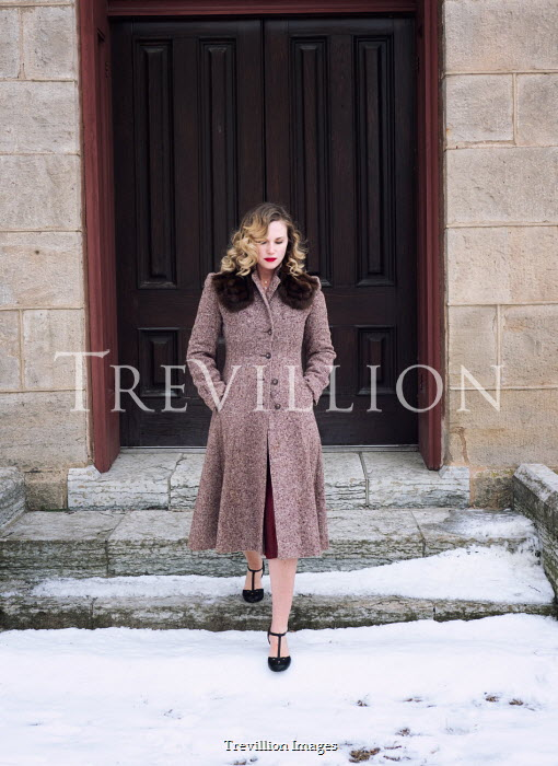 Elisabeth Ansley Woman in vintage coat walking on steps in winter