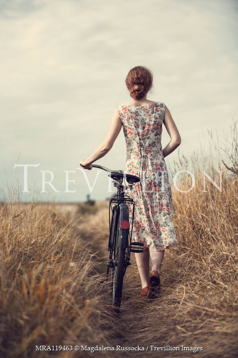 Magdalena Russocka woman with bike walking in countryside