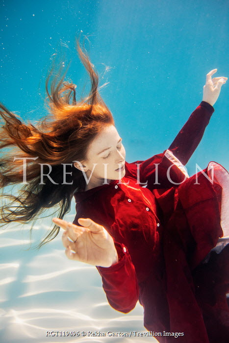 Rekha Garton Young woman in red vintage dress underwater