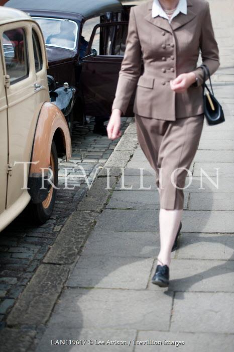 Lee Avison 1940s woman walking past vintage cars