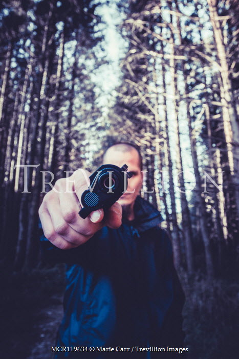 Marie Carr CLOSE UP OF MAN POINTING GUN IN FOREST Men