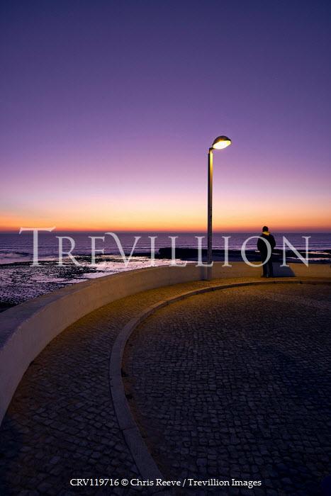 Chris Reeve MAN STANDING BY LAMPPOST WATCHING SEA AT SUNSET Men