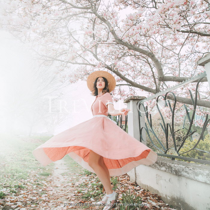 Jovana Rikalo WOMAN IN FLOWING DRESS BY TREE IN BLOSSOM Women
