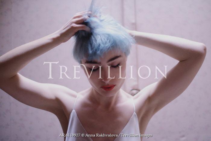 Anna Rakhvalova CLOSE UP OF WOMAN WITH BLUE HAIR TOUCHING HEAD Women
