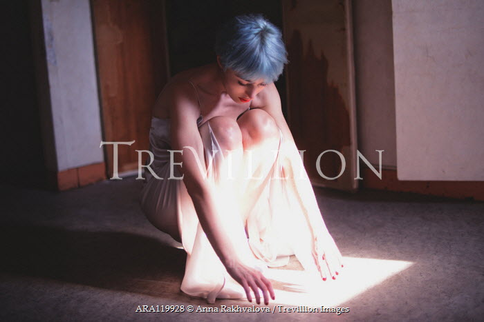 Anna Rakhvalova WOMAN WITH BLUE HAIR CROUCHING IN REFLECTED SUNLIGHT Women