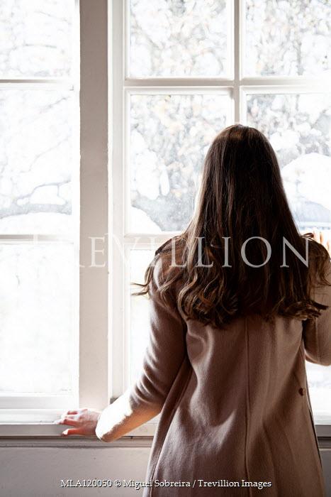 Miguel Sobreira Woman in brown coat by window