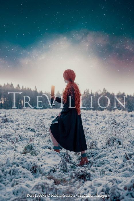 Rekha Garton Woman in black dress walking in snowy field with candlestick