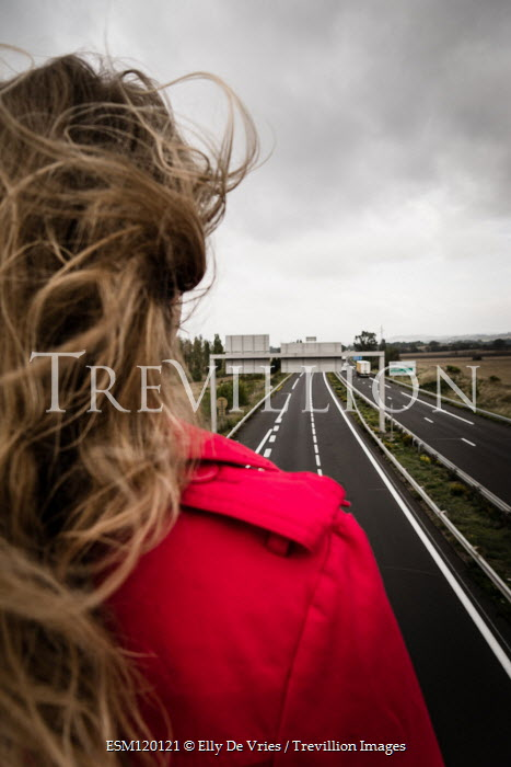 Elly De Vries Young woman by road in wind