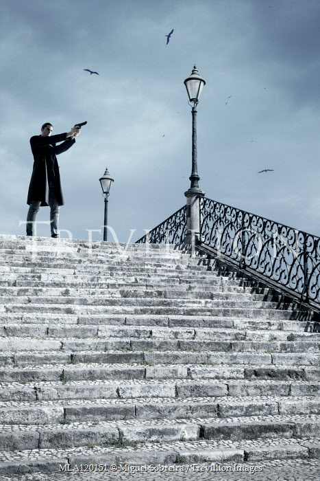 Miguel Sobreira Young woman with black coat and gun on stone steps