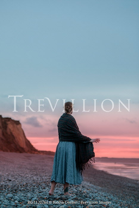 Rekha Garton WOMAN WITH SHAWL STANDING ON BEACH AT SUNSET Women