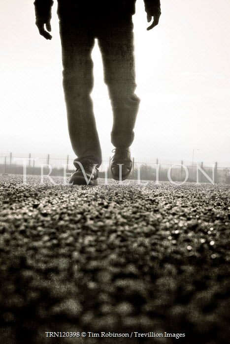 Tim Robinson SILHOUETTED MAN WALKING ON ROAD Men