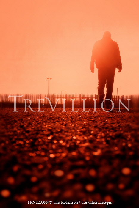 Tim Robinson SILHOUETTED MAN WALKING ON ROAD AT SUNSET Men
