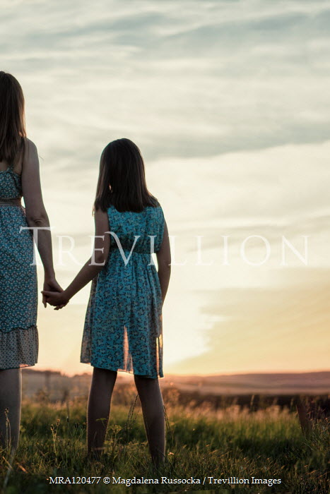 Magdalena Russocka mother and daughter holding hands at sunset in countryside Children