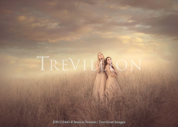 Jessica Drossin TWO GIRLS IN PINK DRESSES STANDING IN FIELD Women