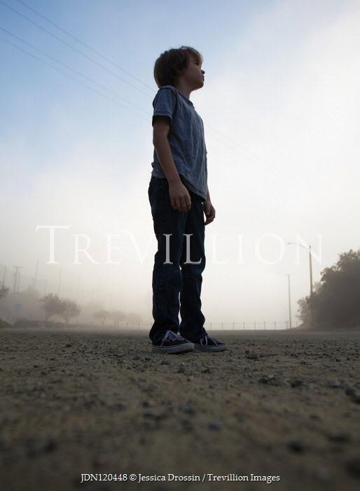 Jessica Drossin LITTLE BOY IN JEANS STANDING ON ROAD Children