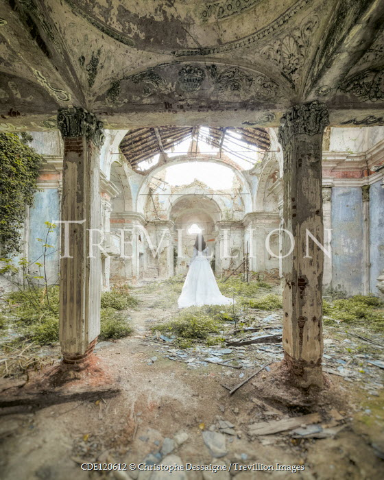Christophe Dessaigne Young woman in white dress standing in ruins
