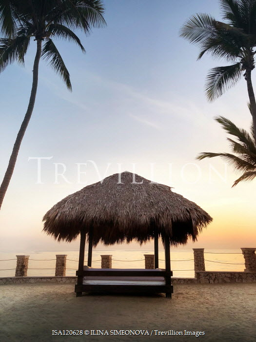 ILINA SIMEONOVA Thatched roof over bench under palm trees at sunset