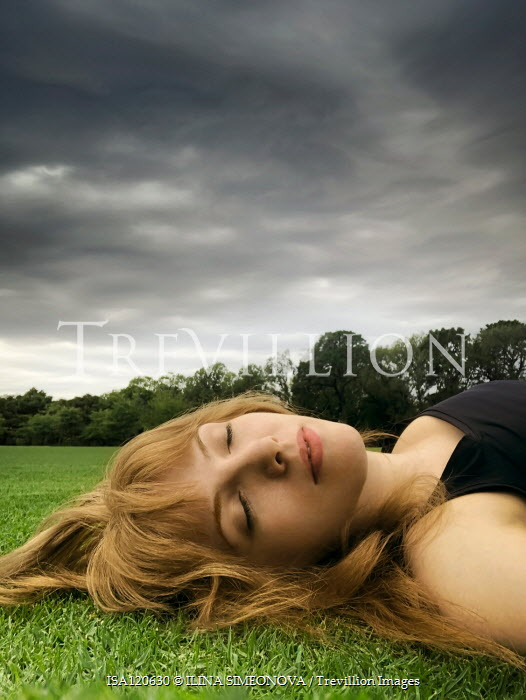 ILINA SIMEONOVA Young woman lying in grass