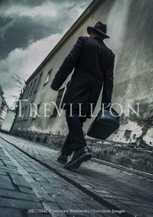 Jaroslaw Blaminsky Man in black hat and coat walking in city