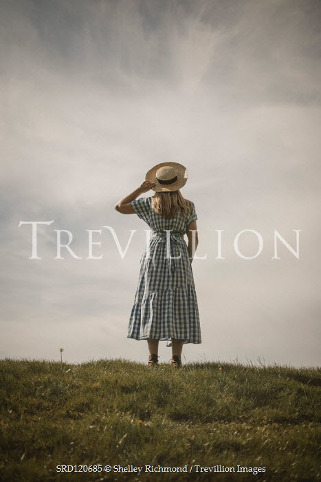 Shelley Richmond Young woman in vintage checked dress and sun hat standing on hill