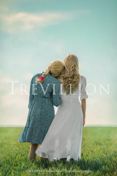 Ildiko Neer Two blonde women standing in summery field Women