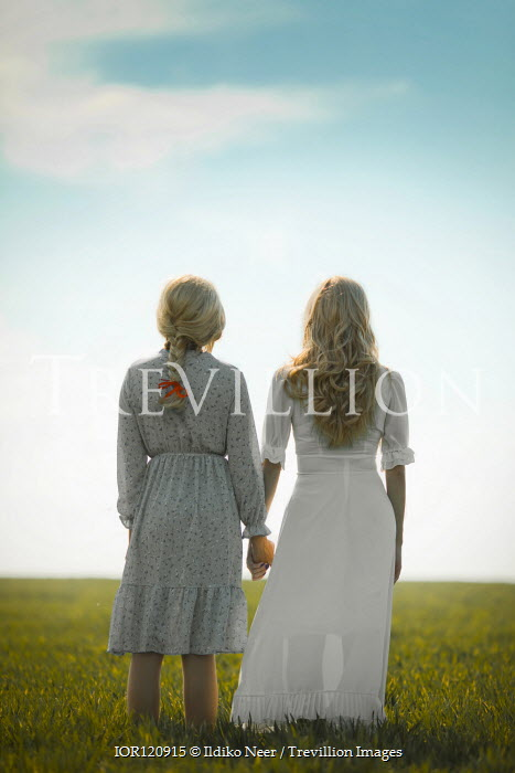 Ildiko Neer Two women standing in field hand in hand
