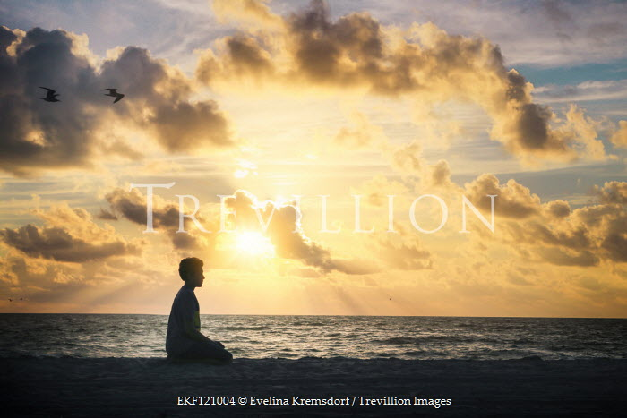 Evelina Kremsdorf Boy sitting on beach at sunset