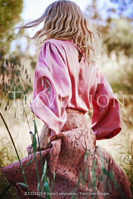 Irene Lamprakou Young woman in pink walking in field