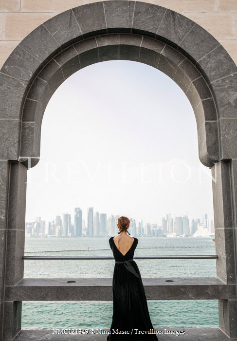 Nina Masic WOMAN STANDING BY ARCHWAY WATCHING RIVER AND CITYSCAPE Women