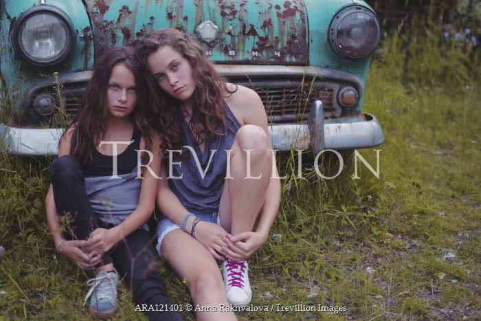 Anna Rakhvalova TWO SAD GIRLS SITTING BY RUSTY CAR Children